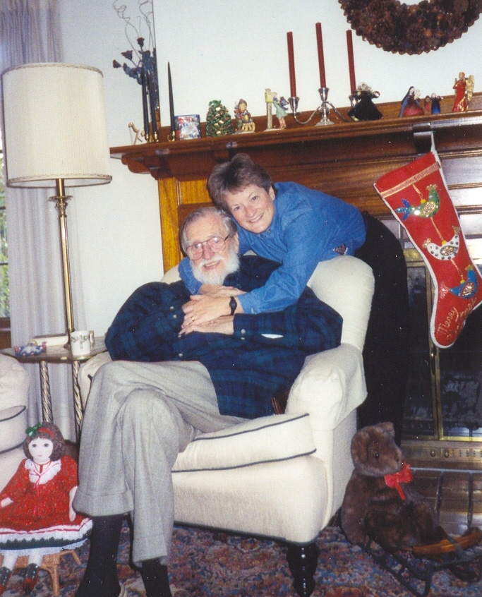 Walter Kramer sits in a chair, hugged from behind by his daughter Mary Jo Chapman. They are surrounded by Christmas decor.