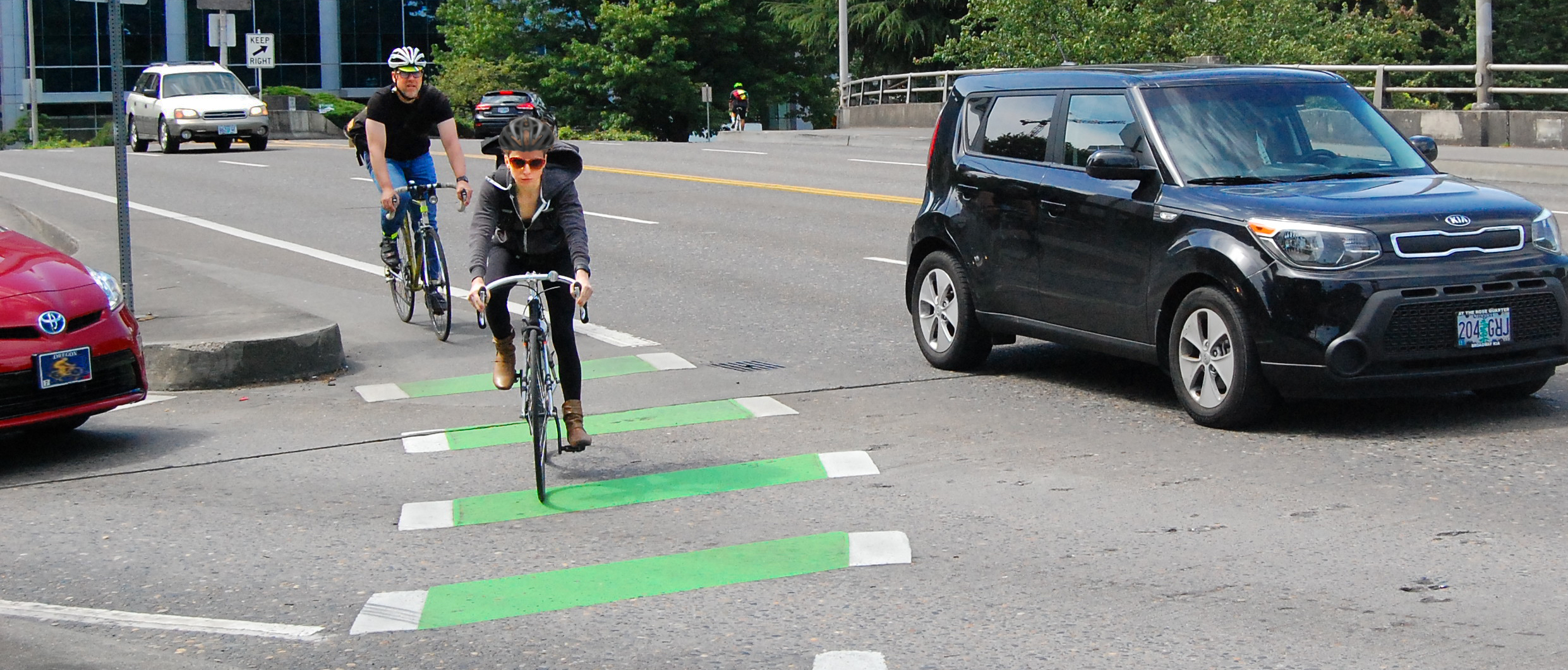 Bicyclists ride in a painted bike lane, defined by green stripes