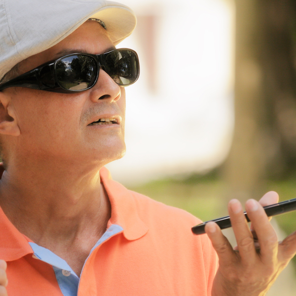A man wearing sunglasses and a cap uses his mobile phone close to his face