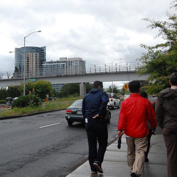 Two people walk on a sidewalk