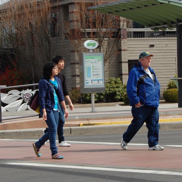 Three pedestrians walking on a crosswalk