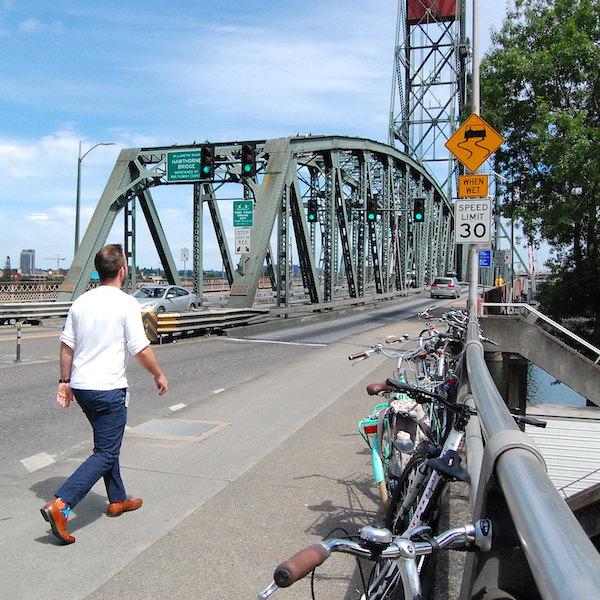 A pedestrian walking on a sidewalk on a bridge