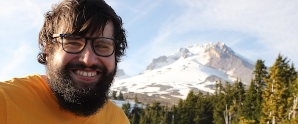 Jaime Orrego-Onate, wearing glasses and an orange T-shirt, faces the camera with a mountain in the background.