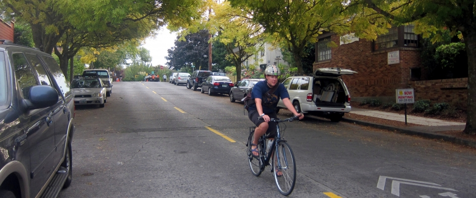 A bicyclists rides down a neighborhood greenway