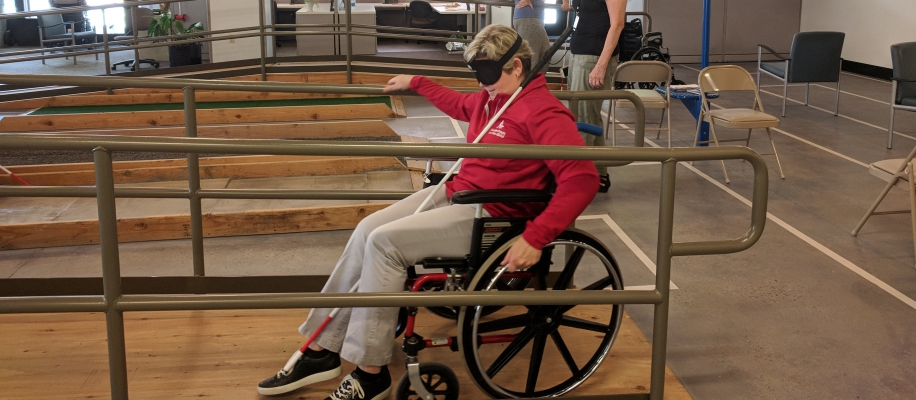 A blindfolded woman navigates a wheelchair up a ramp