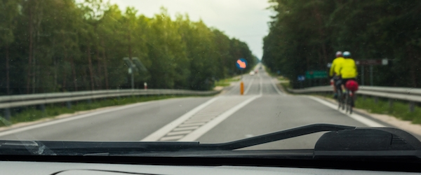 A view through the front windshield of a car, with two bicyclists on the road ahead.