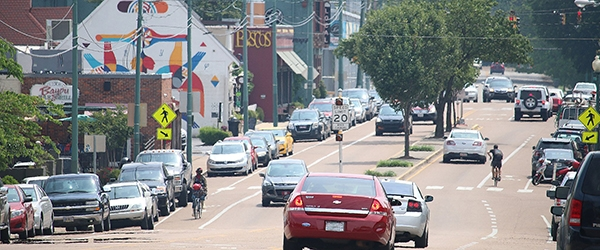 Bicyclists ride past retail establishments