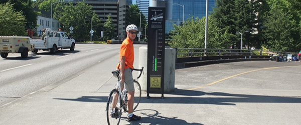 Cyclist stands next to the Hawthorne Bridge Bicycle Counter