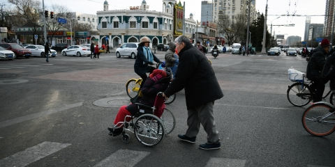 A woman on a yellow bicycle and a person pushing another person in a wheelchair through a crosswalk