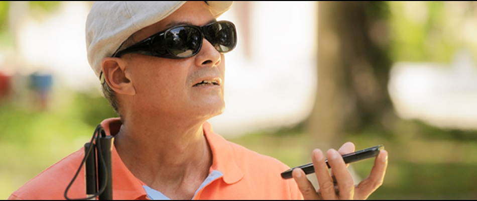 A man with sunglasses and a cane carries a smartphone in his hand, appearing to be listening to its audio