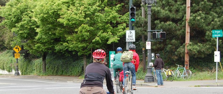 Cyclists riding toward a green bike signal