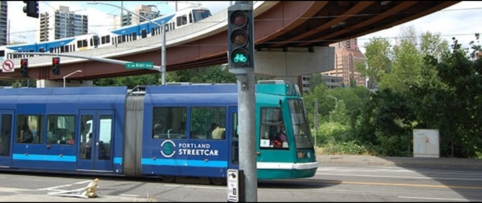 A streetcar crosses a road with a bicycle signal, with a light rail train visible on an overpass overhead.